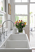 Vase of roses next to white double sinks with tap fittings in kitchen
