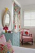 Pale blue chest of drawers and pink-striped armchair in girl's bedroom