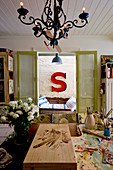 View across painting table to antique bench below large red letter S on brick wall