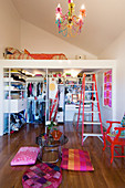 Colourful floor cushions around side table and walk-in wardrobe below loft bed in apartment