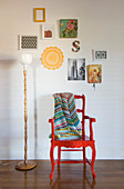 Colourful blanket on red armchair and standard lamp below pictures on white wall