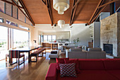 Red sofa, lounge area and dining area next to terrace doors in open-plan interior