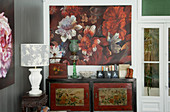 Oriental cabinet below floral artwork and table lamp on antique side table