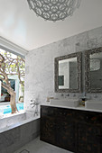 Mirrors above twin sinks and bathtub next to window