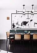 Dining table with chairs and bench in front of modern art