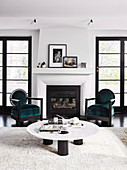 Low coffee table and two chairs in front of the fireplace in the living room