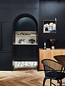 Black fixtures and arched neckline with a view of the kitchen