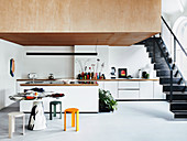 Bright, open kitchen with black metal stairs to the gallery