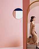Round mirror on pink wall, reflection of woman in oval mirror