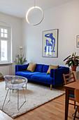 Polstersofa in Königsblau, Retrostuhl und Coffeetable im Wohnzimmer