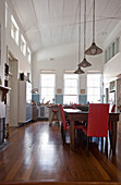 Dining table and kitchen in double-height interior with arched, white wooden ceiling
