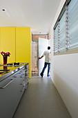 Moderne Küchenzeile und deckenhohe gelbe Schrankwand in Architektenhaus