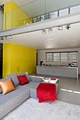 Offener Wohnraum in Architektenhaus mit Galerie und etagenübergreifender gelber Schrankwand