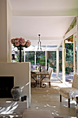 Dining area in glazed conservatory of country-house-style open-plan interior