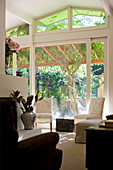 View from interior through sliding doors and onto terrace with climbing plants growing over pergola