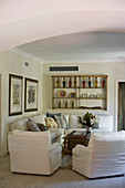 Seating area in country-house style with white corner sofa and loose-covered armchairs