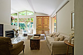 Antique wooden cupboard and sliding doors leading onto terrace in country-house-style living room