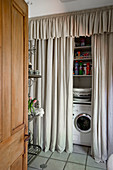 Washing machine and shelves hidden by floor-to-ceiling grey curtain