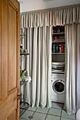 Waschmaschine und Regale versteckt hinter deckemhohen grauem Vorhang