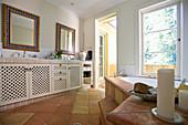 Country-house-style bathroom with terracotta floor tiles