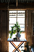 Vase of small folding table in front of window in rustic wooden cabin