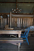Simple bed behind dining table with chair and bench in rustic wooden cabin