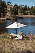 Picknick auf rustikalem Holztisch untern Sonnenschirm am See