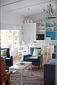Bright open-plan interior in white and blue with kitchen, dining table and seating area