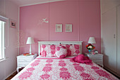 White wooden bed and white bedside cabinets in feminine, pink bedroom