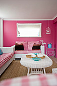 White rattan furniture and pink walls in living room of beach house