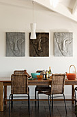 Three pictures of Buddha on wall above wooden dining table with wicker chairs