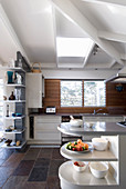 Stone floor tiles and white wood-beamed ceiling in kitchen in modern country-house style