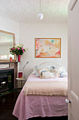 Nude painting above bed with pink bedspread in romantic, feminine bedroom