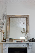Mirror with ornate wooden frame on white marble mantelpiece