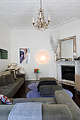 Sofa, marble fireplace and chandelier in small eclectic living room