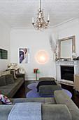 Kleines Wohnzimmer im Stilmix mit Polstersofa, Marmorkamin und Kronleuchter