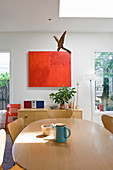 Abstract painting above low sideboard, oval dining table and classic chairs