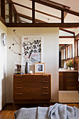 Chest of drawers in bedroom below sloping ceiling and exposed wooden ceiling beams