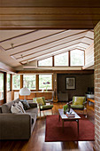 Fifties-style living room with wooden floor, brick walls and sloping ceiling