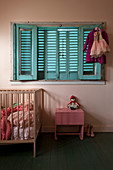 Cot below bed with blue shutters in pink, vintage nursery