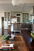 Wooden coffee table in vintage-style, open-plan interior with stainless steel kitchen in background