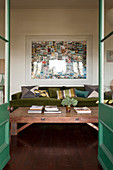 View through open, green double doors to coffee table and moss-green sofa