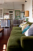 Moss-green sofa and stainless steel kitchen in vintage-style, open-plan interior