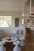 White wooden bench, coffee table and stools in seating area