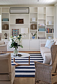 White fitted shelving in seating area with pale rattan and upholstered furniture