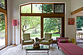 Retro furniture in interior with large wood-framed windows