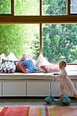 Window seat with storage below large window with garden view