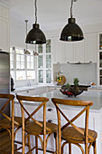 Bentwood barstools at island counter in white, modern, country-house kitchen