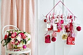 DIY advent calendar in white, red and pink with a bouquet of flowers in front of it on a chair