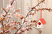 Paper nesting box ornament hanging from branches of cherry blossom